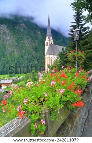 St Vincent church surrounded by vivid flowers in overcast day, Heiligenblut, Austria - stock photo