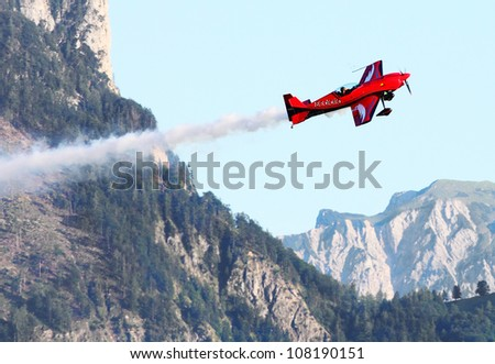 ST. WOLFGANG, AUSTRIA - JULY 7: The Zivko Edge 540 aircraft piloting most popular austrian aerobatic pilot Hannes Arch during a famous Air Challenge on July 7, 2012 in St. Wolfgang.