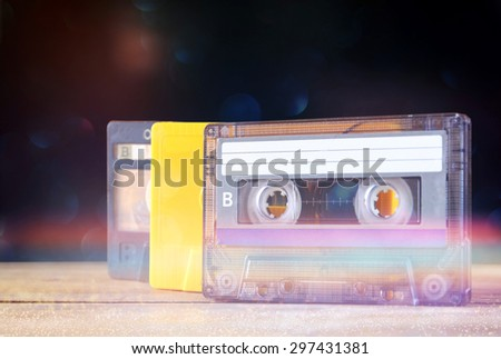 stack Cassette tapes over wooden table. retro filtered with glitter overlay - stock photo