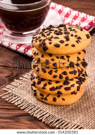 Stack cookies with chocolate on sackcloth with cup of coffee