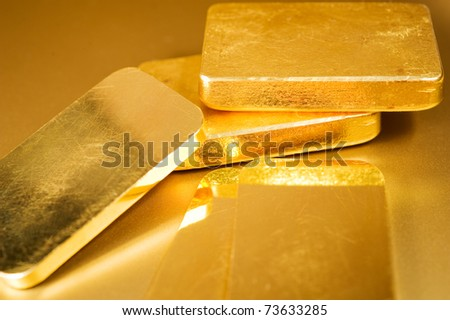 stack fine gold ingots on a golden background - stock photo