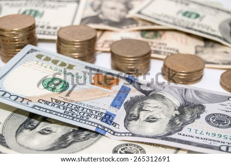 Stack gold coins in graph and US currency dollar bills - stock photo