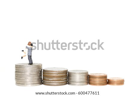 Stack money coin with couple hugging on white background
