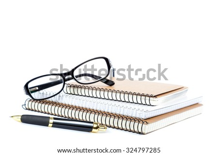 Stack notebook, pen and glasses isolated on white background. - stock photo
