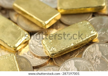Stack of actual smallest gold bar commonly sold in Thailand over pile of dollar coins. Each bar is 96.5% purity gold which is roughly equal to 99.5% purity 2.527 troy ounce. - stock photo