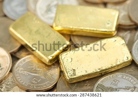 Stack of actual smallest gold bar commonly sold in Thailand over pile of dollar coins. Each bar is 96.5% purity gold which is roughly equals to 99.5% purity 2.527 troy ounce. - stock photo