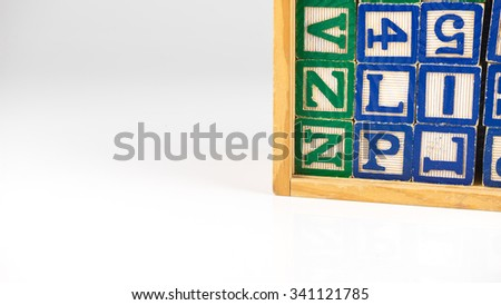 Stack of alphabet block letters and numbers in a cube wooden box. Concept of basic structure of spelling education. Isolated on white background. Slightly de-focused and close-up shot. Copy space.