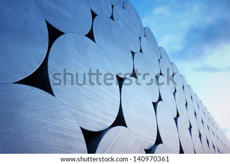 Stack of aluminium billets on a cloudy sky background. Suitable for any industrial related purposes. - stock photo