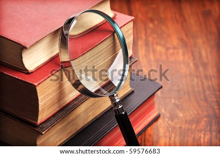 Stack of antique books with magnifying glass on wooden table - stock photo