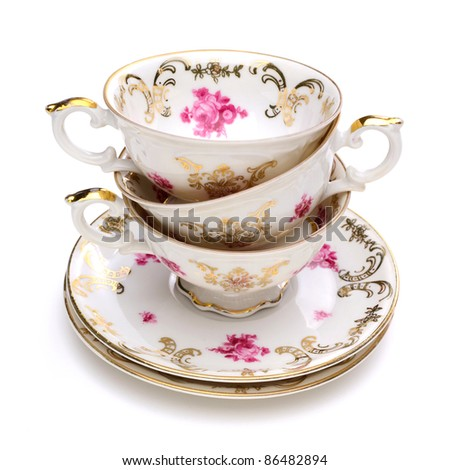 Stack of antique tea cups on white background - stock photo