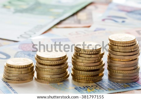 Stack of ascending Euro coins on banknote money background