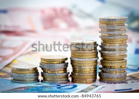 Stack of ascending Euro coins on banknote money background. - stock photo