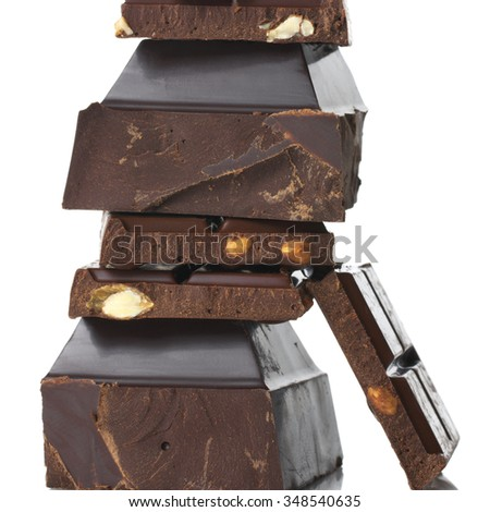 Stack of assorted broken dark chocolate pieces close-up on white background. - stock photo