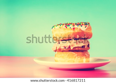 Stack of assorted donuts on a white plate on blue and pink background - stock photo
