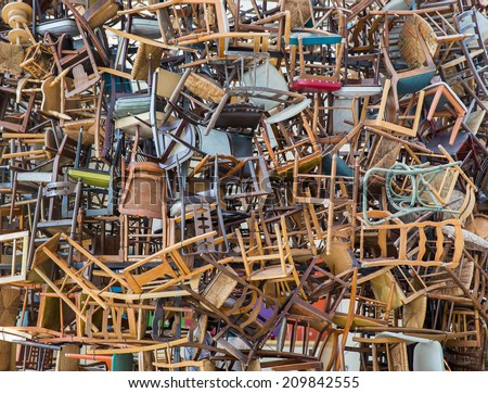 Stack of assorted metal and wooden chairs in random disarray, full frame background image - stock photo