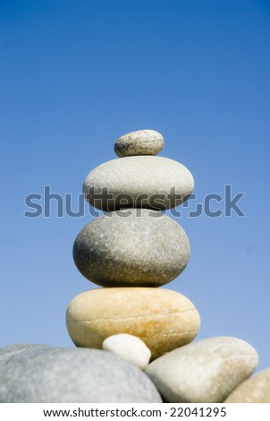 Stack of balanced pebbles, stones against blue sky