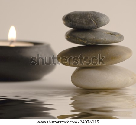 Stack of balanced stones and candle reflected in water. Selective focus.