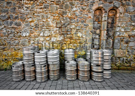 Stack of beer kegs against a rough stone wall - stock photo