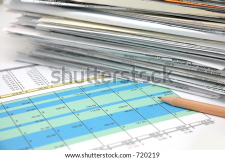Stack of bills and spreadsheet - stock photo