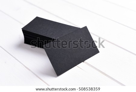 stack of black business cards on a white wooden table