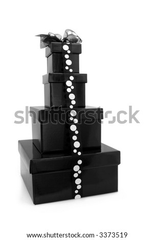 Stack of black gift boxes decorated with black and white polka-dot ribbon. - stock photo