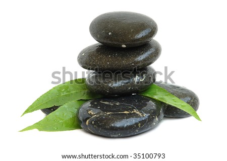 Stack of black stones for hot stones spa treatment and green leaves on white background