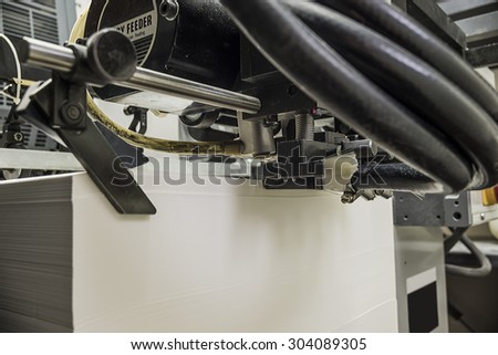 stack of blank paper in a sheetfed offset printing machine - stock photo