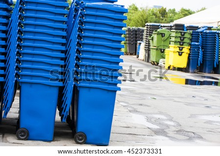 Stack of blue and green industrial trash bins with other bins in the background. - stock photo