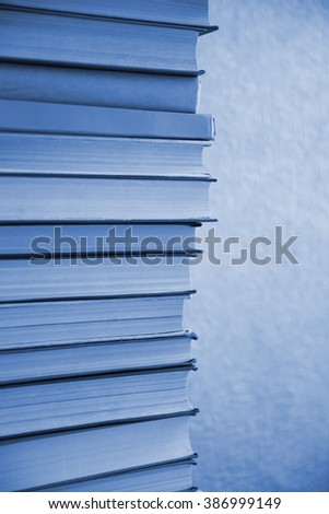 Stack of blue books on light blue background - stock photo