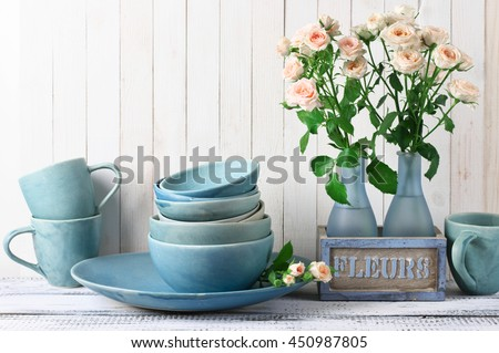 Stack of blue handmade ceramic bowls, dish, mugs and pink roses bouquet in rustic vase against white wooden wall.