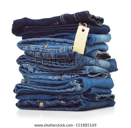 Stack of blue jeans and blank card on white background  - stock photo