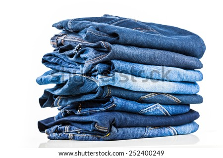 Stack of blue jeans on white - stock photo