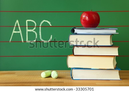 Stack of book and red apple on desk with abc written on the chalkboard - stock photo