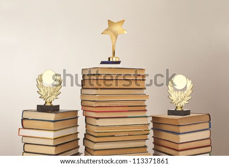 stack of book with a trophy on a gray background, education award space for inscription - stock photo