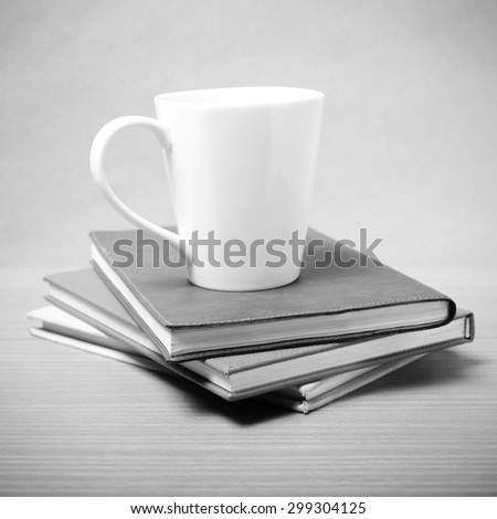 stack of book with coffee mug on wood background black and white tone style
