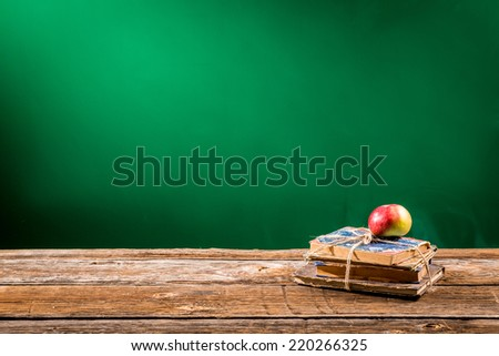 Stack of books and an apple in a classroom - stock photo