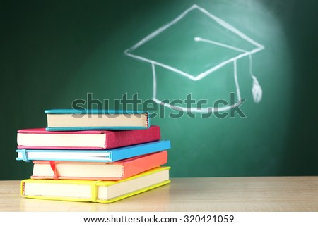 Stack of books and bachelor hat drawing on blackboard background - stock photo
