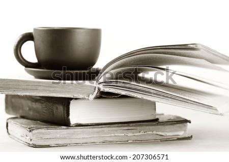 Stack of books and cup on wooden table. Shallow DOF, sepia.