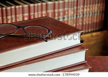 stack of books and glasses detail with the bottom shelf - stock photo