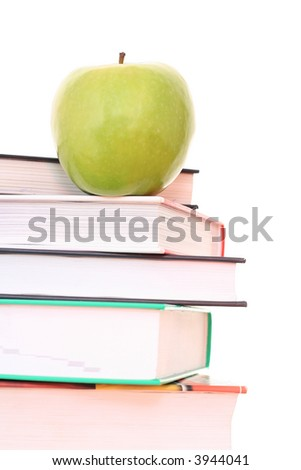 stack of books and green apple on desk - isolated on white