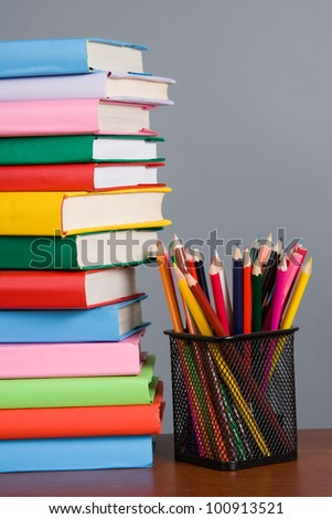 Stack of books and pencils on a gray background
