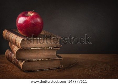 Stack of books and red apple on wooden table - stock photo