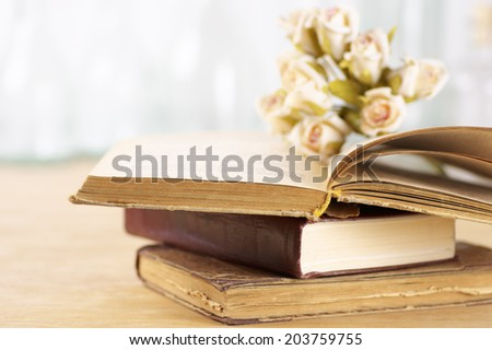 Stack of books and roses on wooden table. Shallow DOF. - stock photo