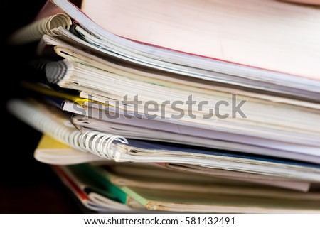Stack of books background. many books piles. High books stack on wooden shelf background.