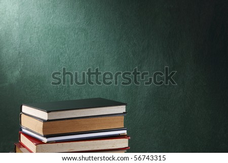 stack of books in front of the black board