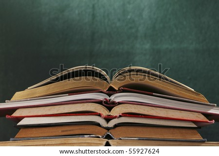 stack of books in front of the blackboard - stock photo