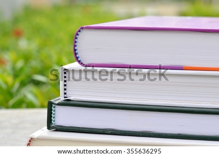 Stack of books in the garden. - stock photo