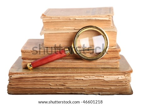 Stack of books, magnifying glass isolated on white - stock photo