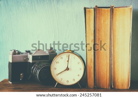 stack of books, old clock and vintage camera over wooden table. image is processed with retro faded style - stock photo