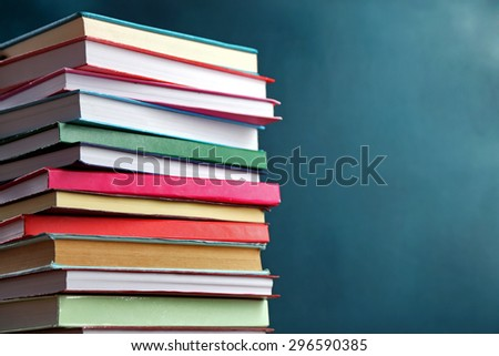 Stack of books on blackboard background - stock photo